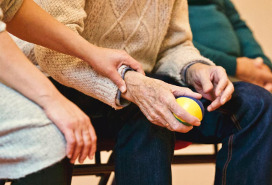 hand comforting older man holding a stress ball