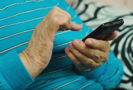 elderly person's hands using cell phone